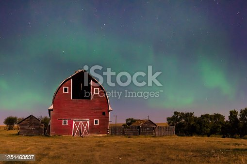 Northern Lights over an abandoned, red vintage barn in Saskatchewan, Canada