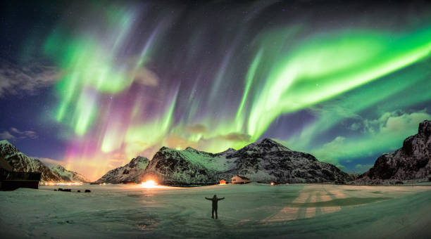 aurora borealis (northern lights) over mountain with one person - clima polar imagens e fotografias de stock
