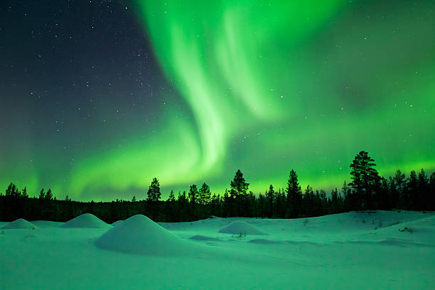 aurora borealis over snowy landscape winter, finnish lapland - finland stock pictures, royalty-free photos & images
