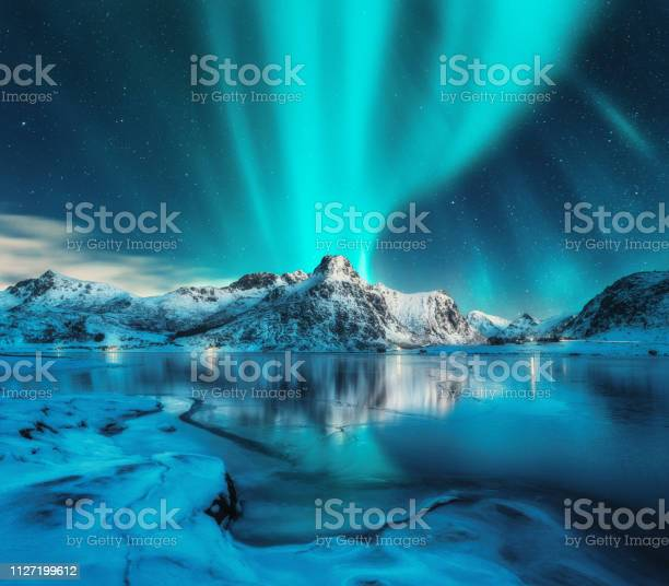 Photo of Aurora borealis over snowy mountains, frozen sea coast, reflection in water at night. Lofoten islands, Norway. Northern lights. Winter landscape with polar lights, ice in water. Starry sky with aurora