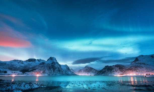 Aurora borealis over the sea coast, snowy mountains and city lights at night. Northern lights in Lofoten islands, Norway. Starry sky with polar lights. Winter landscape with aurora reflected in water stock photo
