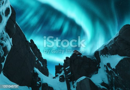Aurora borealis over the snow covered mountain peak in Lofoten islands, Norway. Northern lights in winter. Night landscape with polar lights, snowy rocks. Starry sky with aurora. Beautiful nature