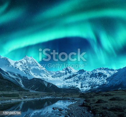 Aurora borealis over the snowy mountains, coast of the lake and reflection in water. Northern lights above snow covered rocks. Winter landscape with polar lights, lake. Starry sky with bright aurora
