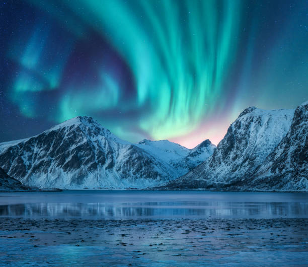 Aurora borealis over the snowy mountains, coast of the lake and reflection in water. Northern lights above snow covered rocks. Winter landscape with polar lights, fjord. Starry sky with bright aurora stock photo