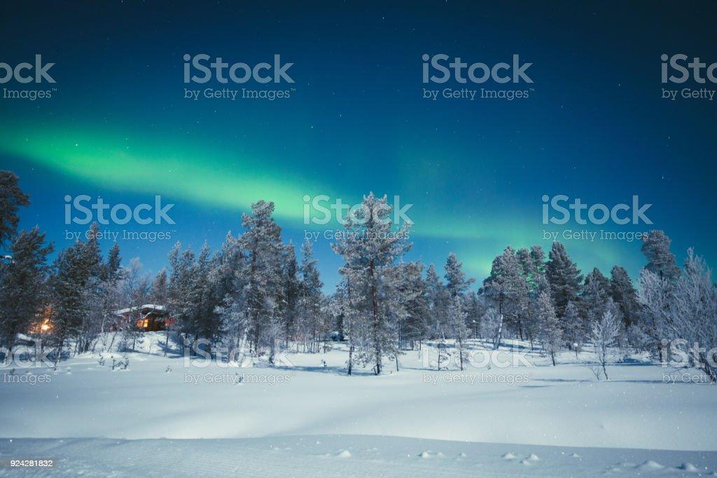 Aurora Borealis over winter wonderland scenery in Scandinavia stock photo