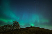 People watching aurora borealis on top of an ancient grave hill in old Uppsala during a very active storm. Its very rare to see auroras this powerful in Uppsala