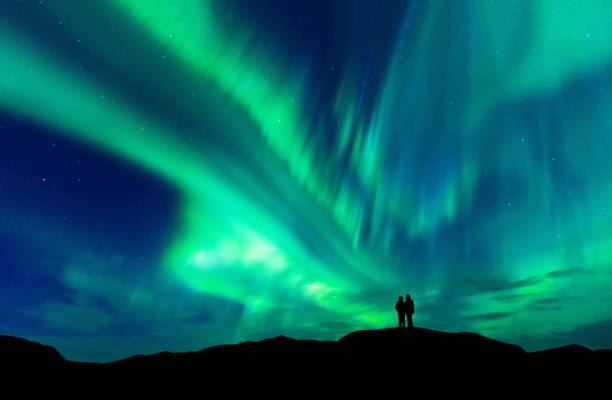 aurora borealis with silhouette love romantic couple on the mountain.honeymoon travel concept - aurora boreale foto e immagini stock