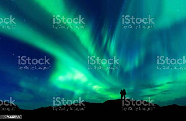 Photo of Aurora borealis with silhouette love romantic couple on the mountain.Honeymoon travel concept