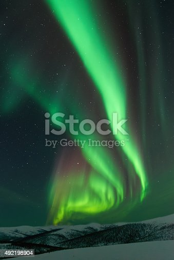 istock Aurora Borealis with snow covered mountain tops in winter 492198904