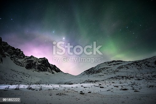 istock Aurora borealis with sunrise shining over mountain range in the night sky 991852222