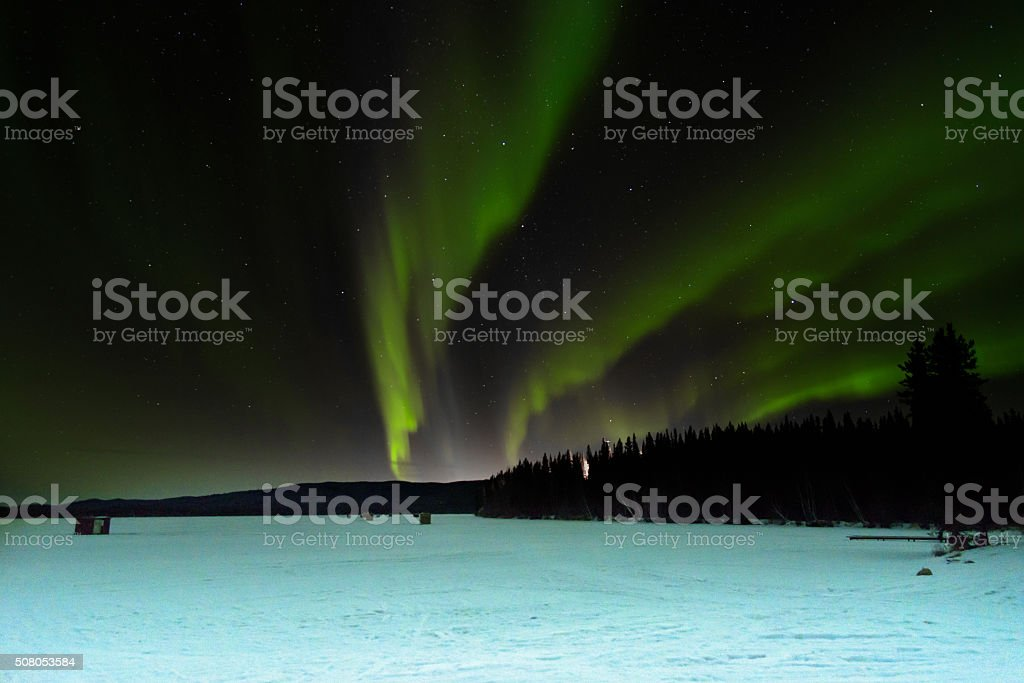 Aurora Over Ice Fishing Houses on Lake in Alaska stock photo