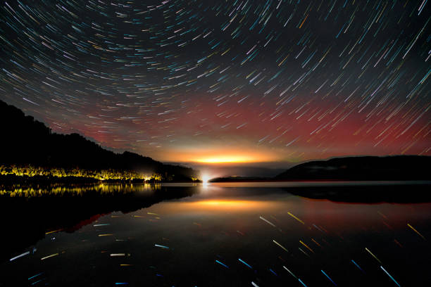 Aurora star trail over the lake at night stock photo