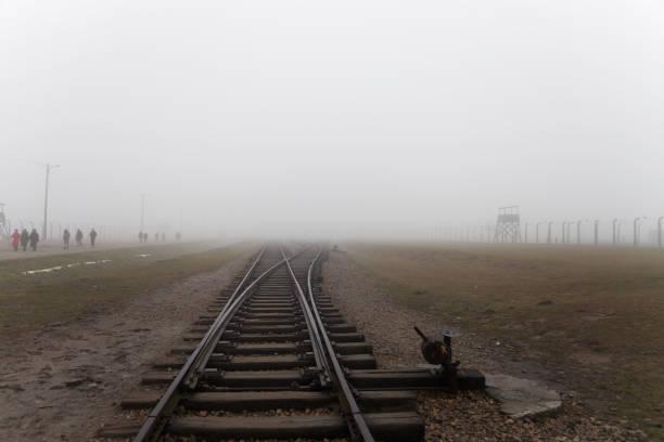 Auschwitz-Birkenau concentration camp. The tracks in the Jewish extermination camp. German death camp in Oświęcim. Barbed wire around from the camp. – zdjęcie