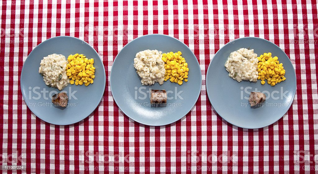 austere food: three modern blue plates on checkered tablecloth stock photo