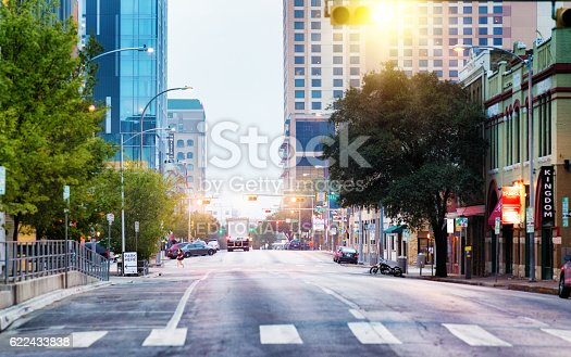 Austin, USA - November 5, 2016: Austin Texas east 5th street panoramic view at dawn. THe street is lined with restaurants, boutiques and hotels. A woman crosses the street running; a few cars are parked and a truck drives off in the distance.