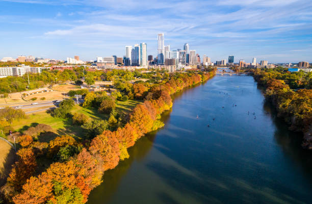 Austin Texas fall colors autumn leaves along Colorado river Austin Texas above lady bird lake , as leaves change during autumn fall colors dramatic line of trees along shore with Austin Texas skyline cityscape downtown skyscrapers in background colorado river stock pictures, royalty-free photos & images