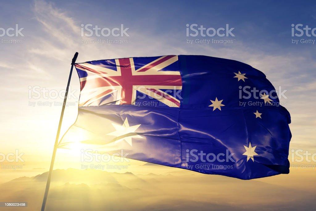 Australia Australian flag textile cloth fabric waving on the top sunrise mist fog stock photo