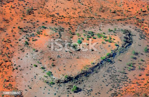 Australia, NT, aerial view over outback with heart-shape formation south of Alice Springs in Chambers Pillar historical reserve on Edge from Simpson Desert,