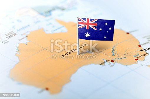 The flag of Australia pinned on the map. Horizontal orientation. Macro photography.