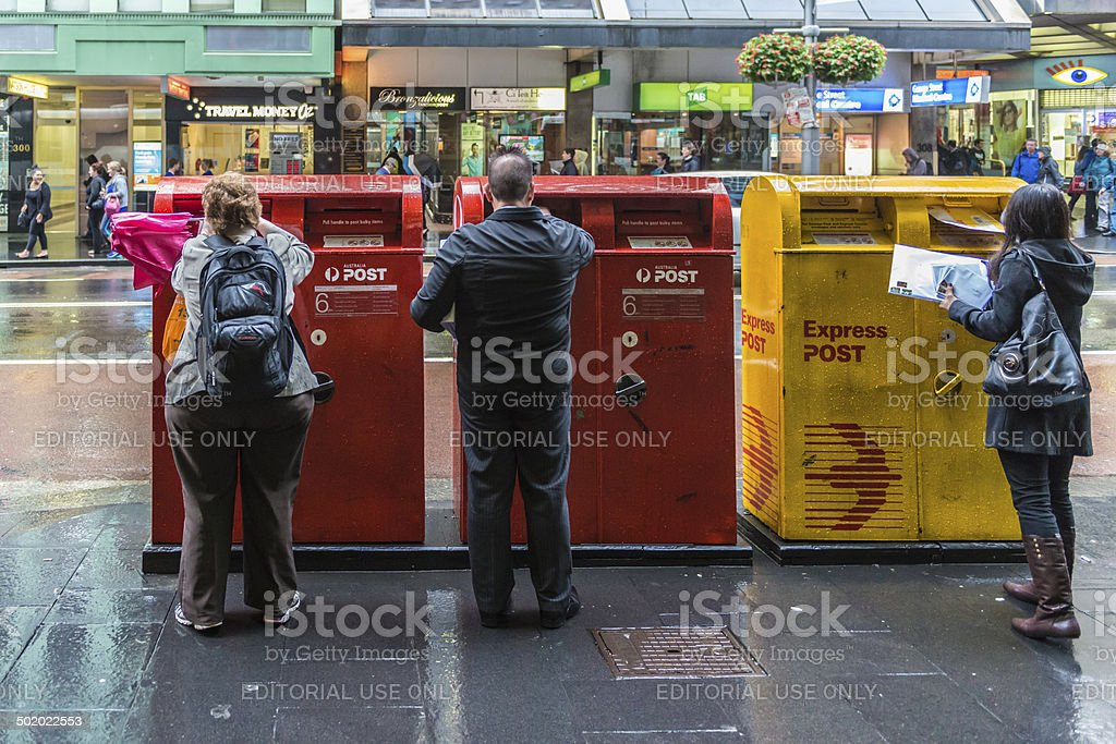 Australia Post Mailboxes. Three persons posting letters, George Street, Sydney​​​ foto