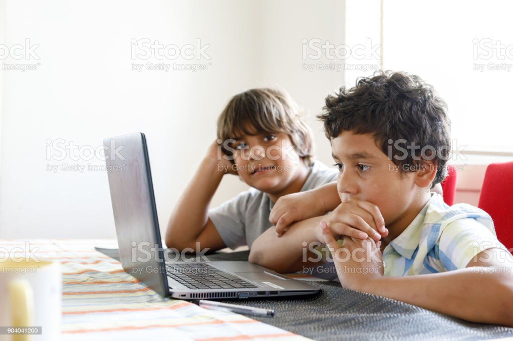 Australian Aboriginal Boys Using Laptop Computer At Home stock photo