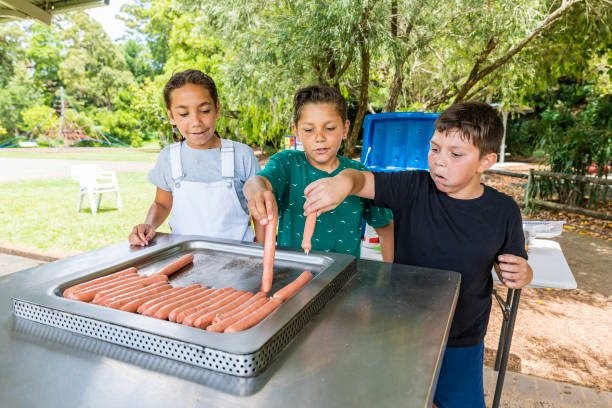 Australian Aboriginal Children Cooking a BBQ For Their Family stock photo