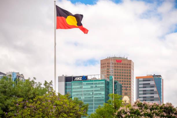 Australian Aboriginal flag above Adelaide skyline Victoria Square in stock photo