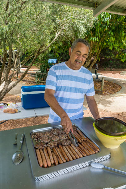 Australian Aboriginal Man Cooking a BBQ For His Family stock photo
