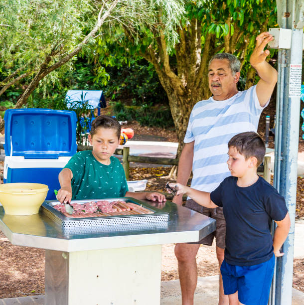 Australian Aboriginal Man Cooking a BBQ With His Family stock photo