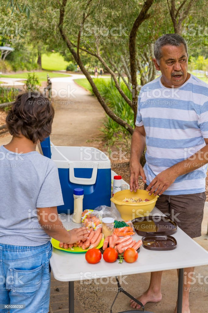 Australian Aboriginal Man Preparing to Cook a BBQ in a Public Park stock photo