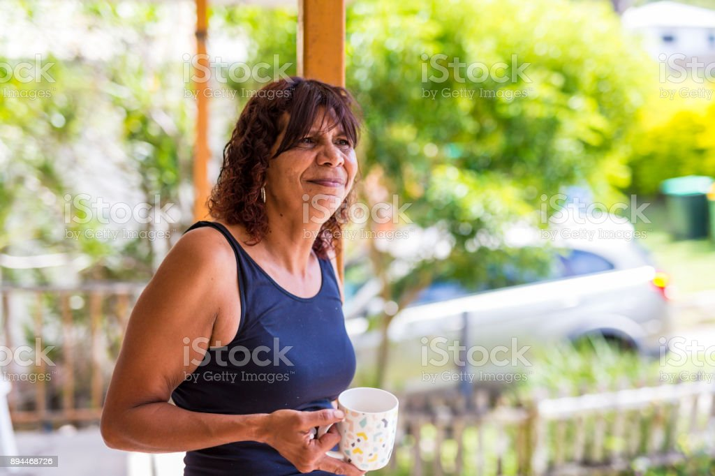 Australian Aboriginal Mutter genießen eine Tasse Kaffee zu Hause – Foto