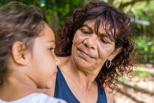 Australian Aboriginal Woman Hugging Her Grandaughter stock photo