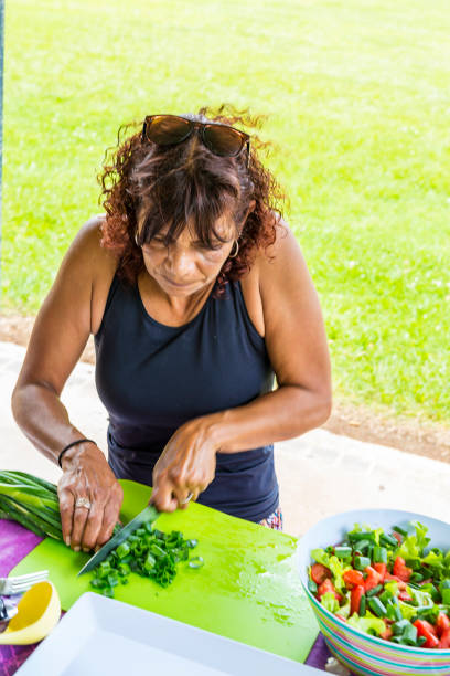 Australian Aboriginal Woman Preparing to Cook a BBQ in a Public Park stock photo
