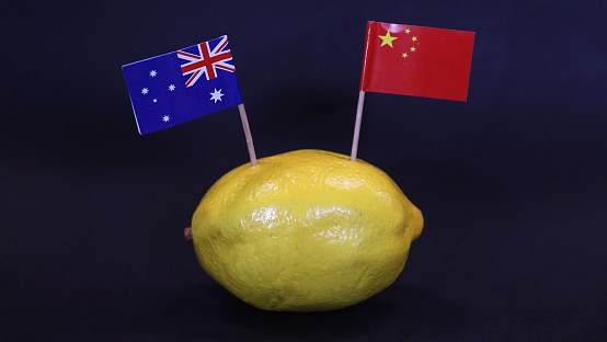 An Australian and Chinese national flag stuck into the skin of a lemon. Souring, sour, bitter relationship between the two countries over trade export and import relations.