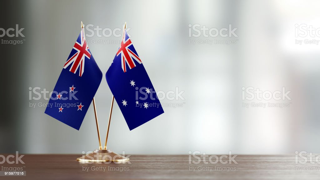 Australian And New Zealand Flag Pair On A Desk Over Defocused Background stock photo