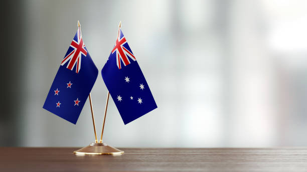australian and new zealand flag pair on a desk over defocused background - new zealand flag stock photos and pictures