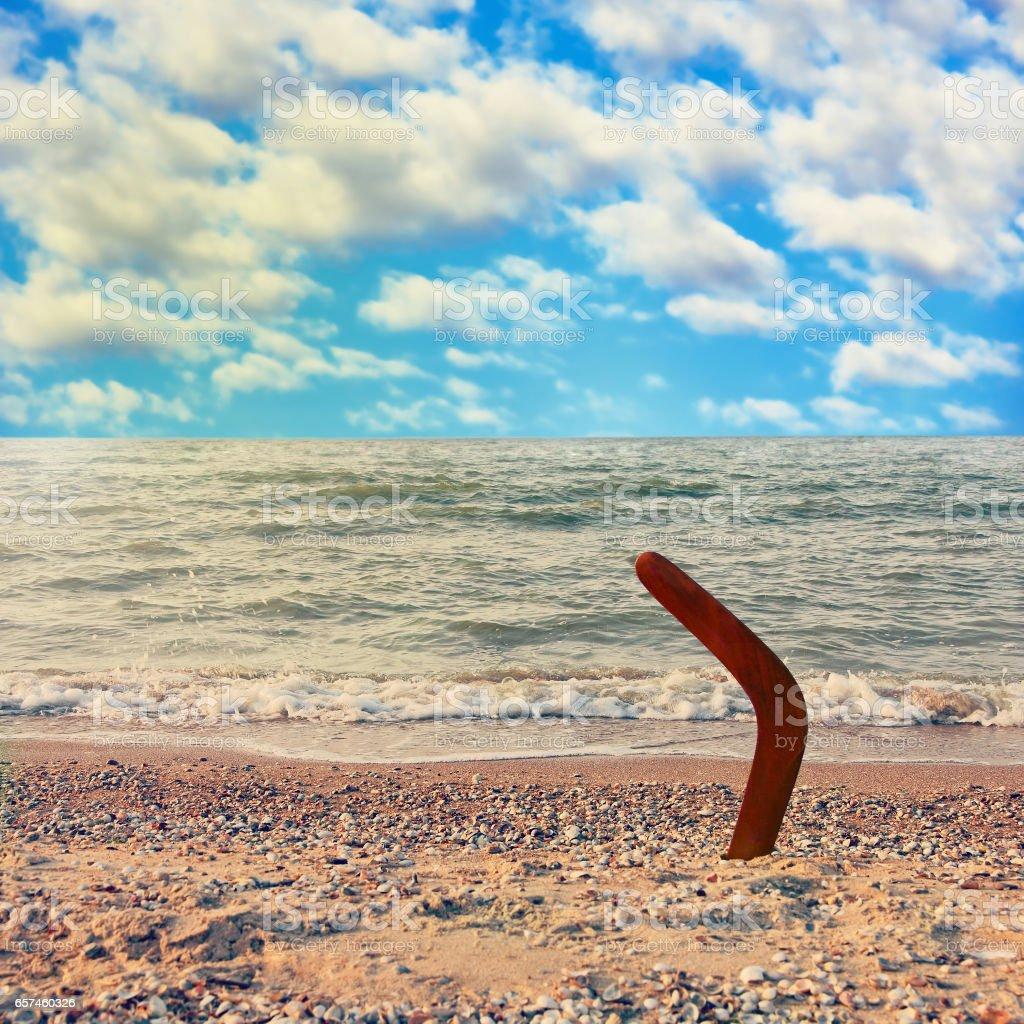 Australian Boomerang on tropical beach against sea wave and blue sky. - Photo