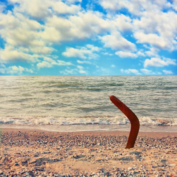 Australian Boomerang on tropical beach against sea wave and blue sky. - foto stock