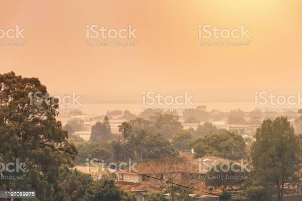 Photo of Australian bushfire: Smoke from bushfires covers the sky and glowing sun barely seen through the smoke. Suburb in a smoke haze. Catastrophic fire danger, NSW, Australia