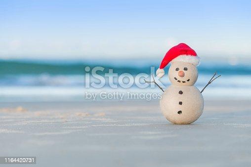 Christmas Sandman - Sandy Snowman on a beautiful sand beach - Christmas symbol of countries where the weather is always warm