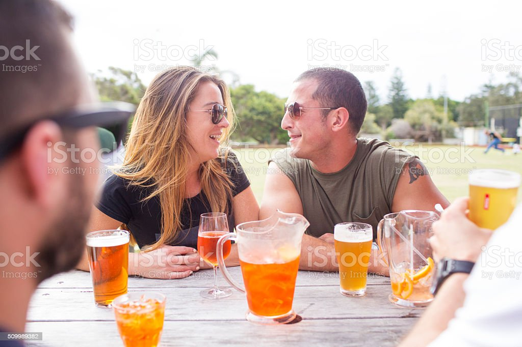 Australian couple drinking with friends in beer garden bowling club stock photo