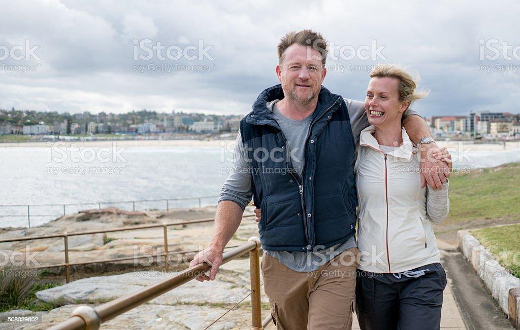 Australian couple walking by the beach stock photo