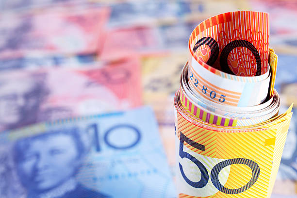 Australian currency rolled up on a currency background stock photo
