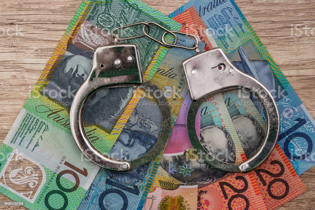 Australian dollar banknotes with handcuffs on wooden table stock photo
