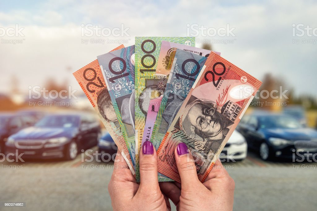Australian dollar in hands on background of new cars stock photo