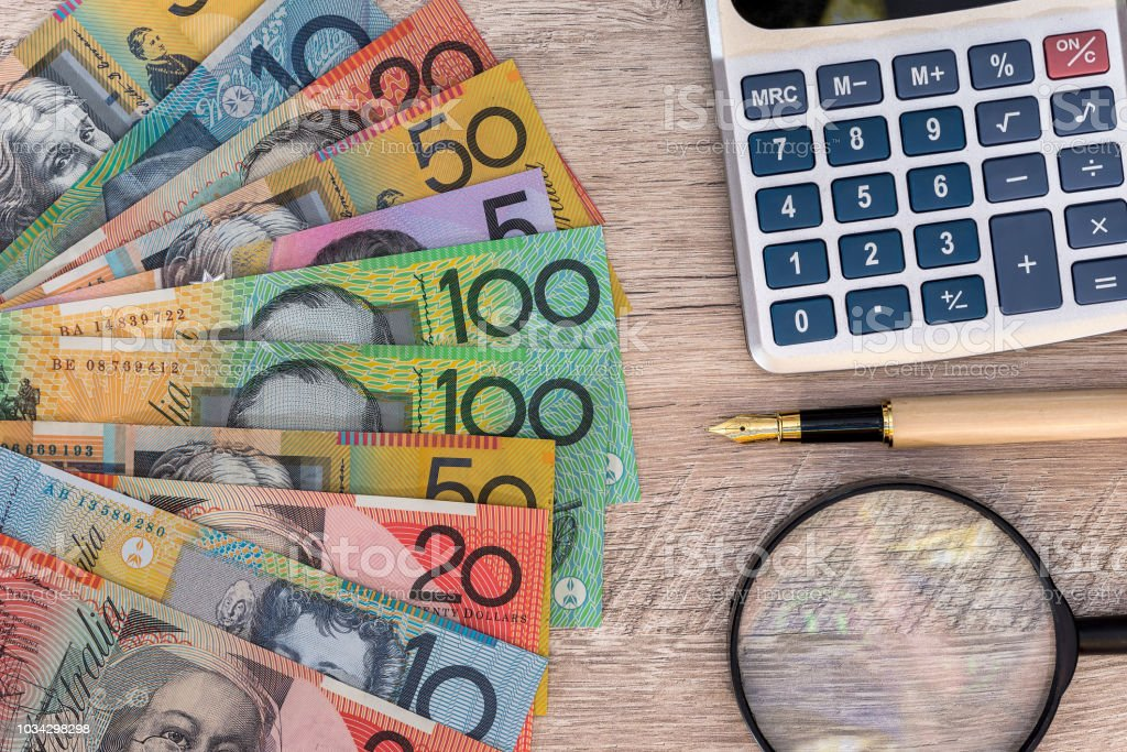 Australian dollars with calculator, pen and magnifier stock photo