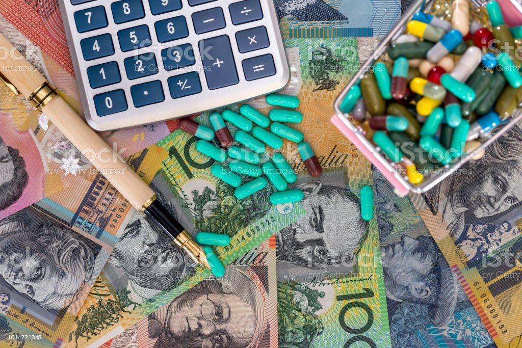 Australian dollars with cart full of pills, pen and calculator stock photo