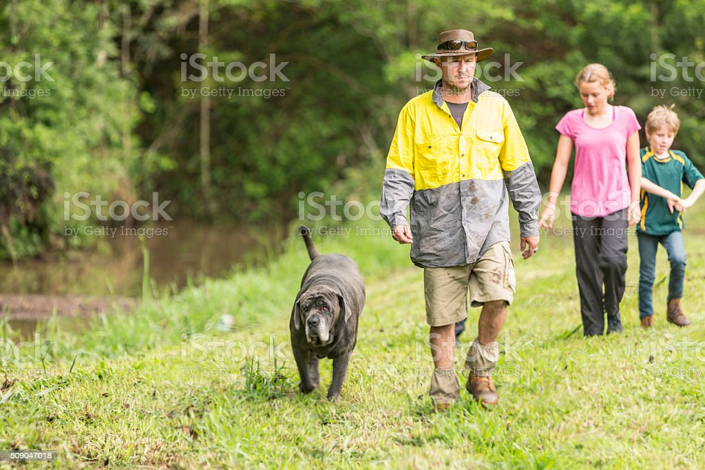 Australian Farmer Walking by a Creek With Dog and Children stock photo
