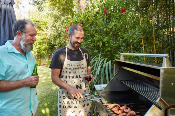 australische vater und sohn vorbereitung grill im sommer - grillschürze stock-fotos und bilder