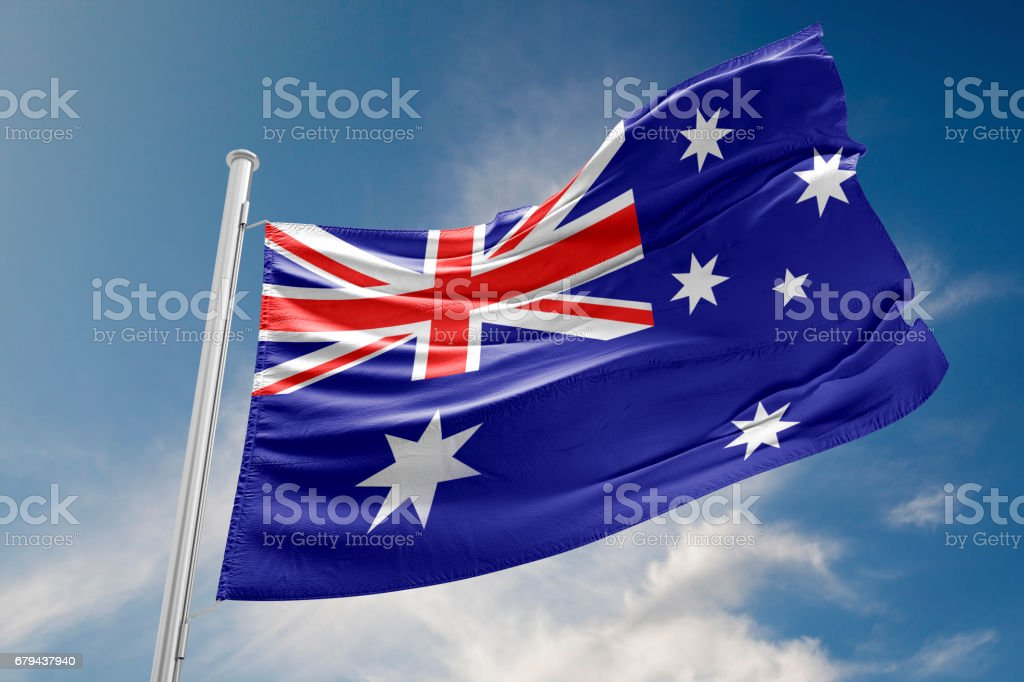 Australian Flag is Waving Against Blue Sky stock photo